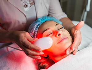 Technician Applying Red Light Therapy on Patient
