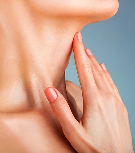 Woman caressing the smooth skin on her neck.